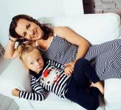 Retrato de la madre y de la hija jovenes sonrientes en casa, fam feliz Fotos de archivo libres de regalías
