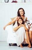 Retrato de la madre y de la hija jovenes sonrientes en casa, fam feliz Imagenes de archivo