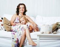 Retrato de la madre y de la hija jovenes sonrientes en casa, fam feliz Imagen de archivo