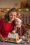 Retrato de la madre y del bebé con la casa de la galleta de la Navidad Foto de archivo libre de regalías