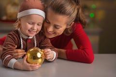 Retrato de la madre y del bebé felices con la bola de la Navidad Fotos de archivo libres de regalías