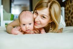 Retrato de la madre y del bebé felices en casa Fotografía de archivo