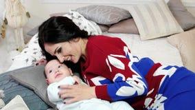Retrato de la madre y del bebé, mujer joven que frota ligeramente, abrazo, acariciando a su hijo joven, la familia en un hogar có almacen de video