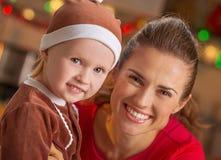 Retrato de la madre y del bebé sonrientes en cocina de la Navidad Imagen de archivo