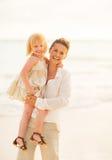 Retrato de la madre y del bebé sonrientes en la playa Imagen de archivo libre de regalías