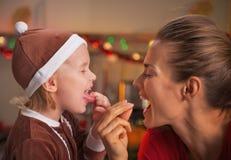 Retrato de la madre y del bebé sonrientes que comen los caramelos coloridos Fotos de archivo
