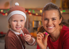 Retrato de la madre y del bebé sonrientes que muestran los caramelos coloridos Imagen de archivo