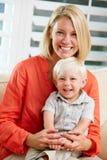 Retrato de la madre y del hijo que se sientan en el sofá en casa Imagen de archivo libre de regalías