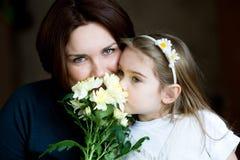 Retrato de la madre y del niño encantadores con las flores imagen de archivo libre de regalías