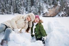 Retrato de la madre y del niño que juegan con la nieve al aire libre Imagen de archivo