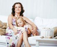 Retrato de la madre y de la hija jovenes sonrientes en casa, fam feliz Fotografía de archivo libre de regalías