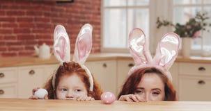 Retrato de la mamá divertida y de su oído del conejito de la hija que lleva con los huevos de Pascua que miran en la cámara Famil metrajes