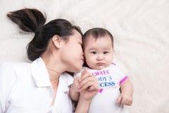 Retrato de la mamá hermosa que juega con sus 6 meses del bebé Foto de archivo libre de regalías