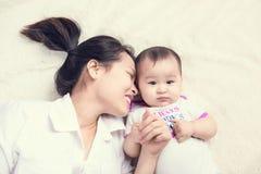 Retrato de la mamá hermosa que juega con sus 6 meses del bebé adentro Imagen de archivo