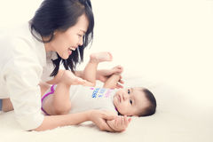 Retrato de la mamá hermosa que juega con sus 6 meses del bebé adentro Foto de archivo