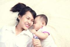 Retrato de la mamá hermosa que juega con sus 6 meses del bebé adentro Foto de archivo libre de regalías