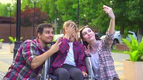 Retrato de la mamá y del papá con una pequeña hija discapacitada en una silla de ruedas que hace un selfie almacen de metraje de vídeo
