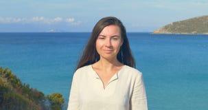 Retrato de la mano corriente hermosa de la mujer joven a través del pelo que sopla en viento en fondo de la playa mediterránea metrajes