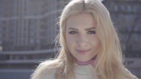 Retrato de la mano de funcionamiento rubia bonita de la mujer con su pelo y la mirada in camera sonriente Paisaje urbano urbano e almacen de metraje de vídeo