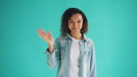 Retrato de la mano que agita y de mirar de la mujer amistosa la cámara con la cara feliz almacen de video