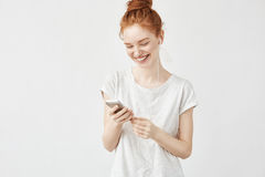 Retrato de la mensajería sonriente y de escuchar de la muchacha bonita del pelirrojo fluir música en auriculares atados con alamb Imagen de archivo