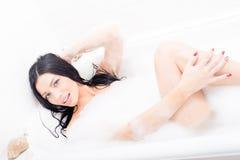 Retrato de la mentira sonriente feliz de la mujer morena joven atractiva atractiva hermosa de los ojos azules en el baño del baln Imagen de archivo