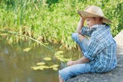 Retrato de la mirada abajo en muchacho que pesca con caña del agua de la charca Imágenes de archivo libres de regalías