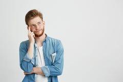 Retrato de la mirada de pensamiento soñadora del hombre joven para arriba con la mano en mejilla sobre el fondo blanco Imagen de archivo