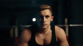 Retrato de la mirada muscular del hombre en la cámara en el gimnasio Concepto de aptitud y de levantamiento de pesas metrajes