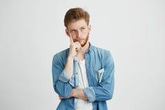 Retrato de la mirada de pensamiento soñadora del hombre joven para arriba con la mano en mejilla sobre el fondo blanco Foto de archivo