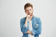 Retrato de la mirada de pensamiento soñadora del hombre joven para arriba con la mano en mejilla sobre el fondo blanco Fotografía de archivo