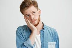 Retrato de la mirada de pensamiento soñadora del hombre joven para arriba con la mano en mejilla sobre el fondo blanco Foto de archivo libre de regalías