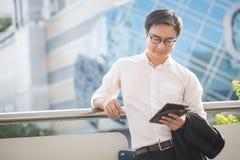 Retrato de la mirada sonriente del hombre de negocios confiada usando la tableta del ordenador Fotografía de archivo