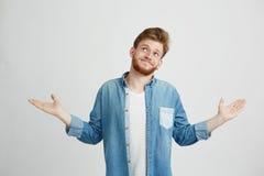 Retrato de la mirada sonriente del hombre hermoso joven para arriba de encogimiento sobre el fondo blanco Foto de archivo