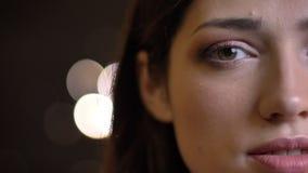 Retrato de la mitad-cara del primer del caucásico bonito joven femenino con los ojos verdes que miran derecho la cámara metrajes