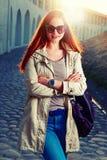 Retrato de la moda de la calle de la mujer astuto-cabelluda joven en vaqueros y de las gafas de sol violetas con un bolso de cuer Imágenes de archivo libres de regalías