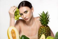 Retrato de la moda de la mujer morena atractiva joven que se sienta por la tabla con las frutas y verduras, sosteniendo las uvas imagenes de archivo
