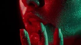 Retrato de la moda de la mujer que toca sus labios con las yemas del dedo en brillo y en las luces de neón en estilo de los años  almacen de video