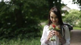 Retrato de la morenita atractiva joven en el vestido del bordado que huele el ramo bonito de flores salvajes en parque verde almacen de metraje de vídeo