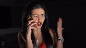 Retrato de la morenita enojada que habla emocionalmente vía el teléfono móvil almacen de video