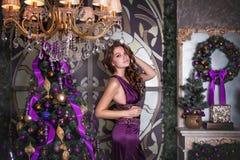 Retrato de la morenita hermosa joven en un vestido violeta cerca de un abeto de la Navidad Imagen de archivo