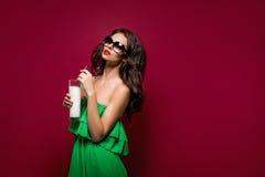 Retrato de la morenita joven hermosa en gafas de sol y dre verde Imagenes de archivo