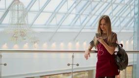 Retrato de la muchacha adolescente alegre que disfruta de música en el accesorio estéreo conectado con el smartphone que entretie almacen de metraje de vídeo