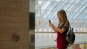Retrato de la muchacha adolescente alegre que disfruta de música en el accesorio estéreo conectado con el smartphone que entretie metrajes