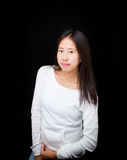 Retrato de la muchacha adolescente asiática que presenta en fondo negro Imagen de archivo