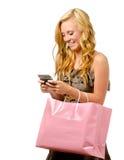 Retrato de la muchacha adolescente con el bolso de compras texting Fotografía de archivo libre de regalías