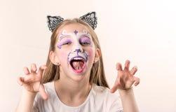 Retrato de la muchacha adolescente con la pintura de la cara del gato Imagenes de archivo