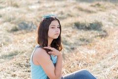 Retrato de la muchacha adolescente en campo con la paja Foto de archivo