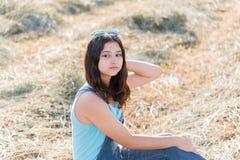 Retrato de la muchacha adolescente en campo con la paja Fotografía de archivo libre de regalías