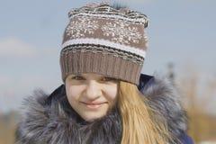 Retrato de la muchacha adolescente en casquillo y chaqueta con el cuello de la piel en invierno afuera Fotografía de archivo